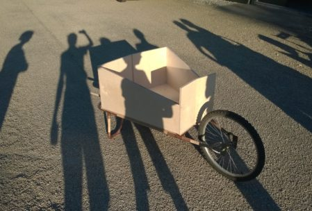 Shadows of people across wheelbarrow